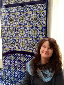 Lara at the Mexican Cultural Institute with Talavera tile in background.